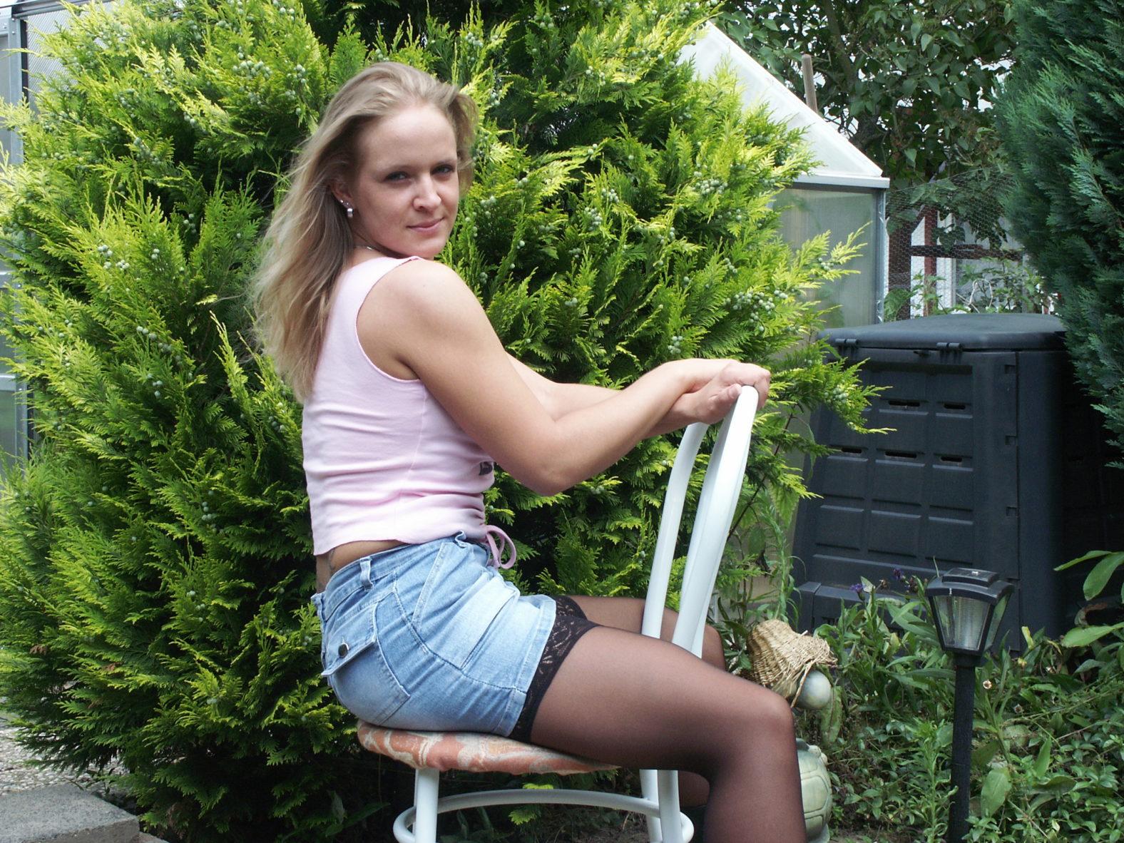 jung Blondine im Unternemd mit halterlosen Strümpfen sitzt auf Stuhl im Garten